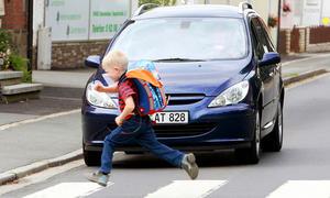 Kind läuft über Zebrastreifen