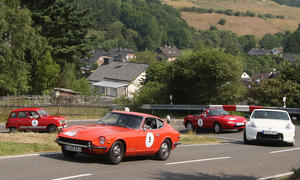 Viele bunte Autos bei der ersten Youngtimer Tour, hier ein orangefarbener Datsun 240Z vor einem Mazda MX-5 NA und einem Renault